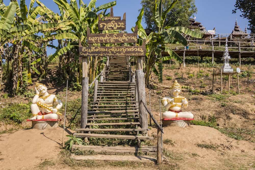 Zwei sitzende Betonfiguren am Aufgang zu Tempel