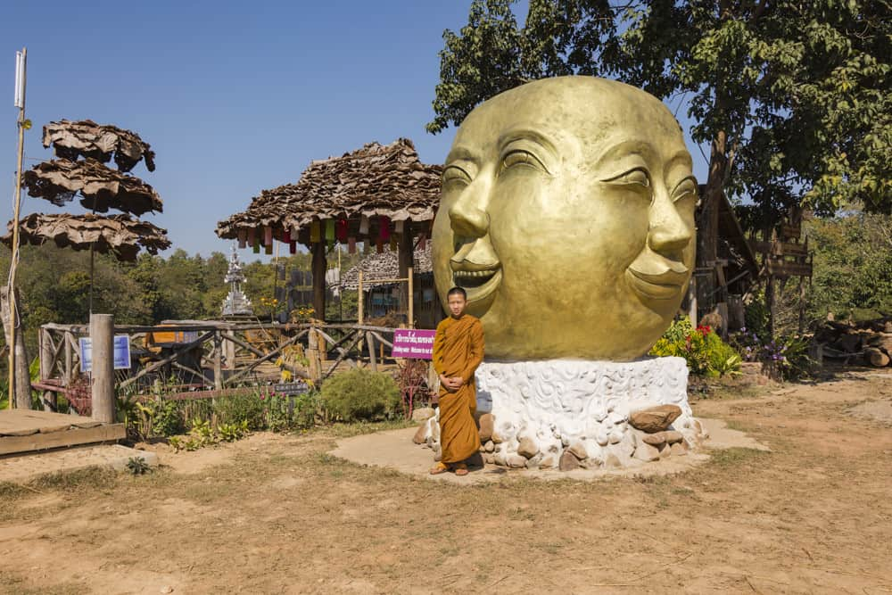 Junger Mönch steht vor einem besonderen Buddha-Kopf
