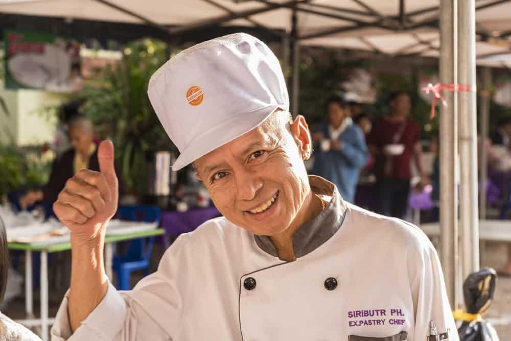 Freundlicher Donut-Bäcker mit Zuckerbächermütze der mich herzlich beim Geburtstag eines Mönches empfängt