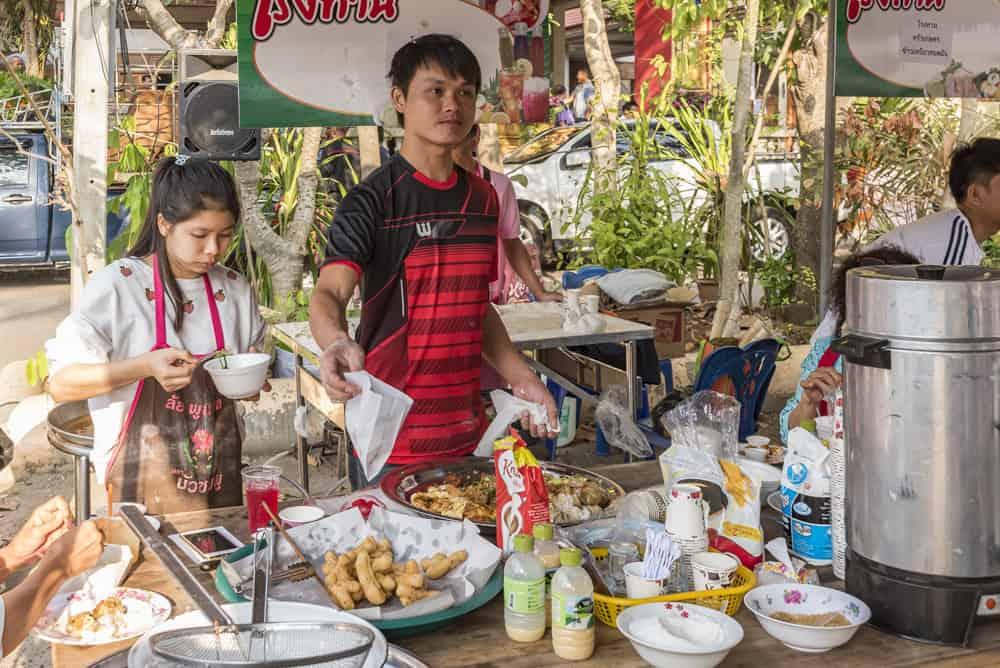 Thailändischer Essenstand bei dem zwei Personen Speisen an die Besucher kostenlos verteilen beim Geburtstag eines Mönches