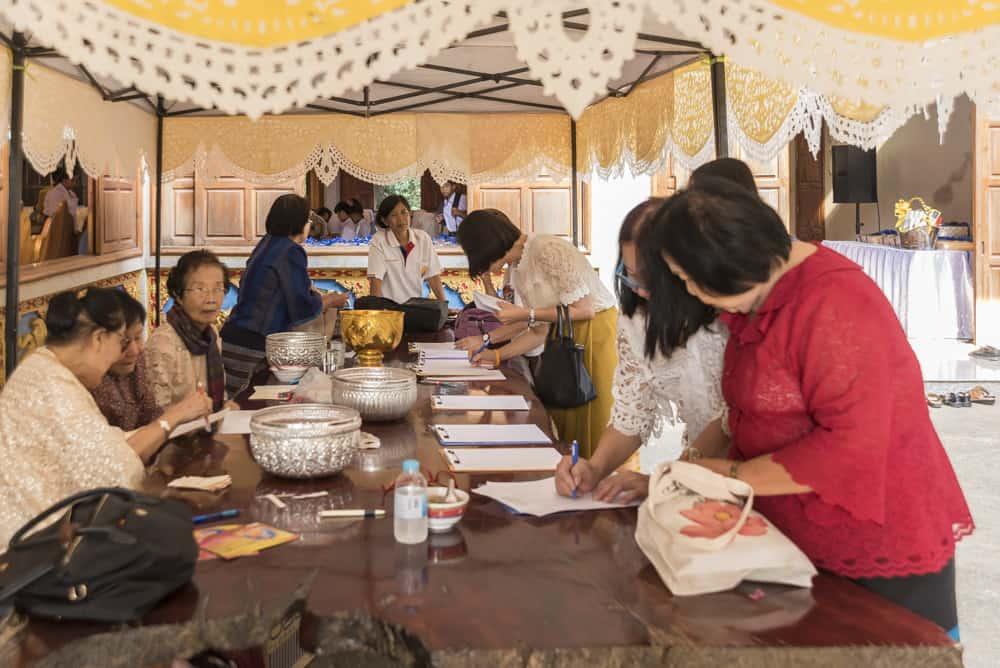 Frauen an einem Tisch sammeln Geld ein als Geschenk für den Tempel