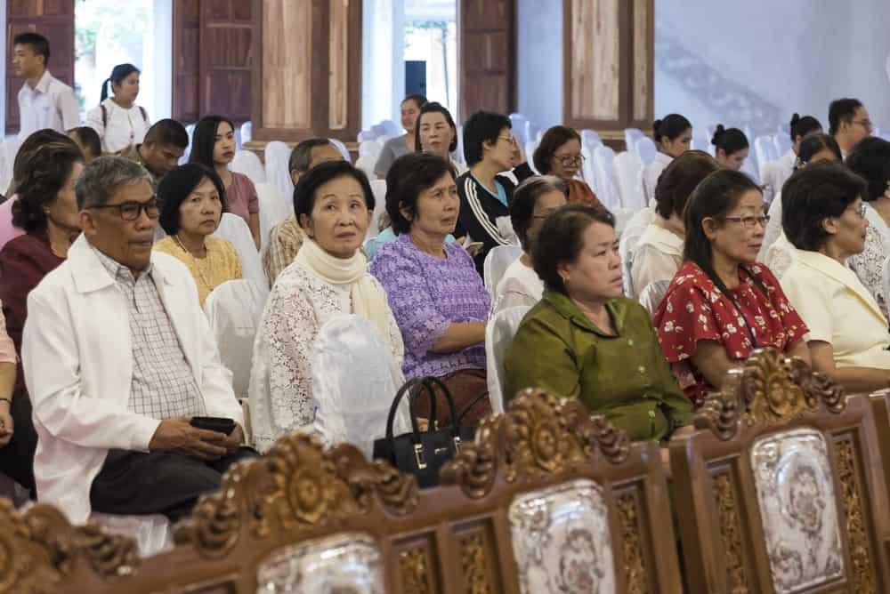 Festlich gekleidete Besucher auf den Stühlen beim Geburtag eines Mönches