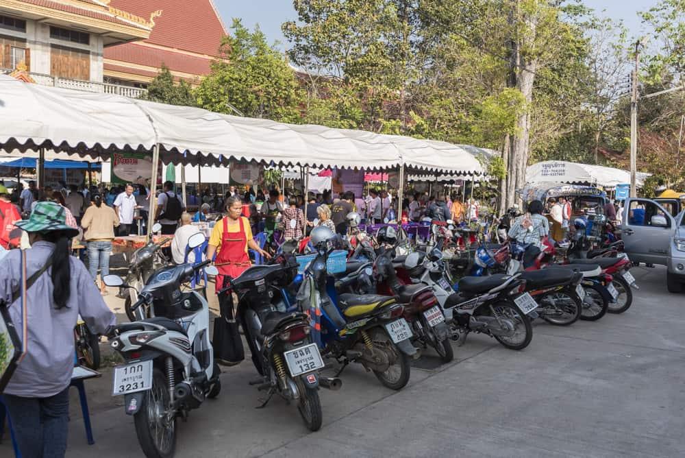 Dicht gedrängt Motorräder und Autos am Eingang des Wat Phet Wararam in Phetchabun