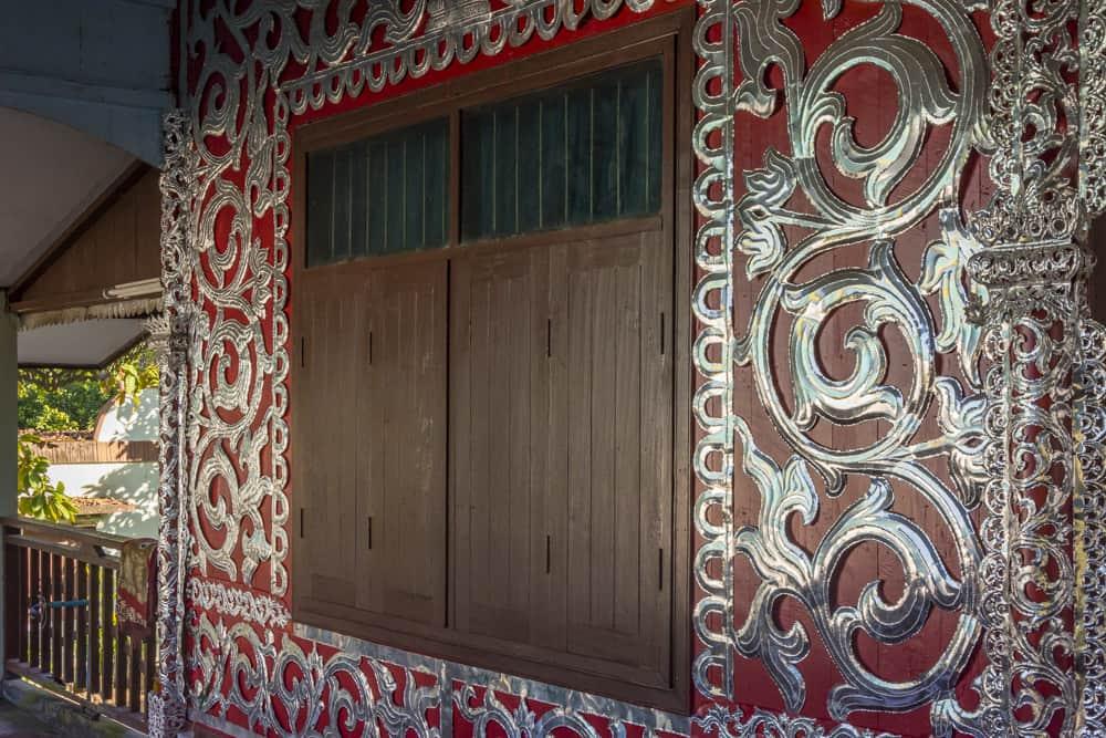 Die rote Farbe der Wände und der kühl wirkende Zinnbeschlag im Wat Chong Kham in Mae Hong Song