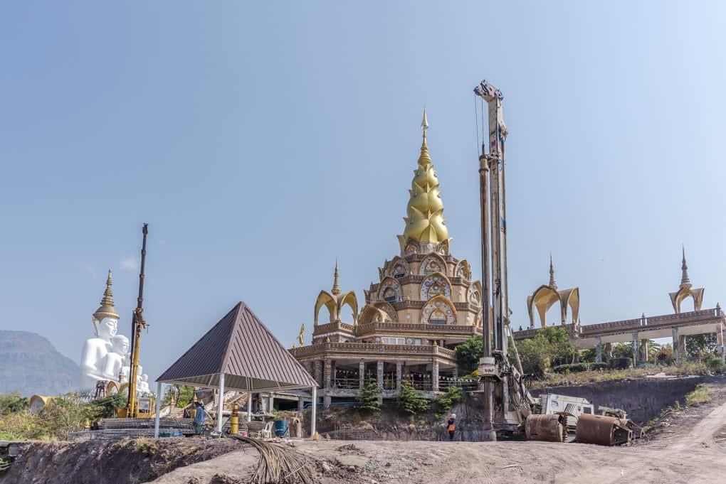 Baustelle im Wat Pha That Pha Son Kaeo dem Tempel mit 5 weißen Buddha-Figuren
