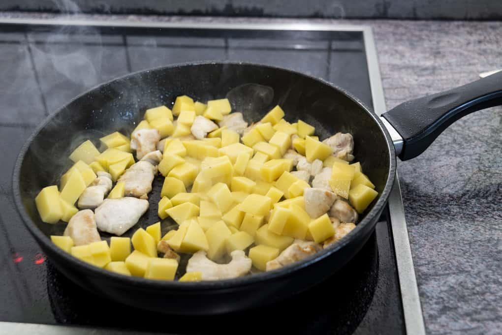 Hühnchen und Kartoffeln für das Curry in der Pfanne