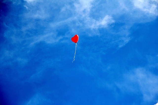Luftballun in Herzform vor blauem Himmel
