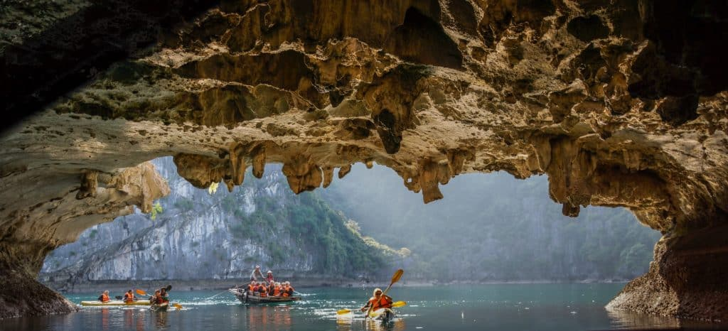 Paddelboote mit Touristen in einer Karsthöhle in der Halog Bucht Vietnam