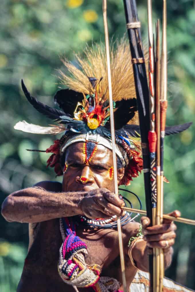 Bedrohlich zielt der Krieger mit Pfeil und Bogen auf uns in Papua Neuguinea