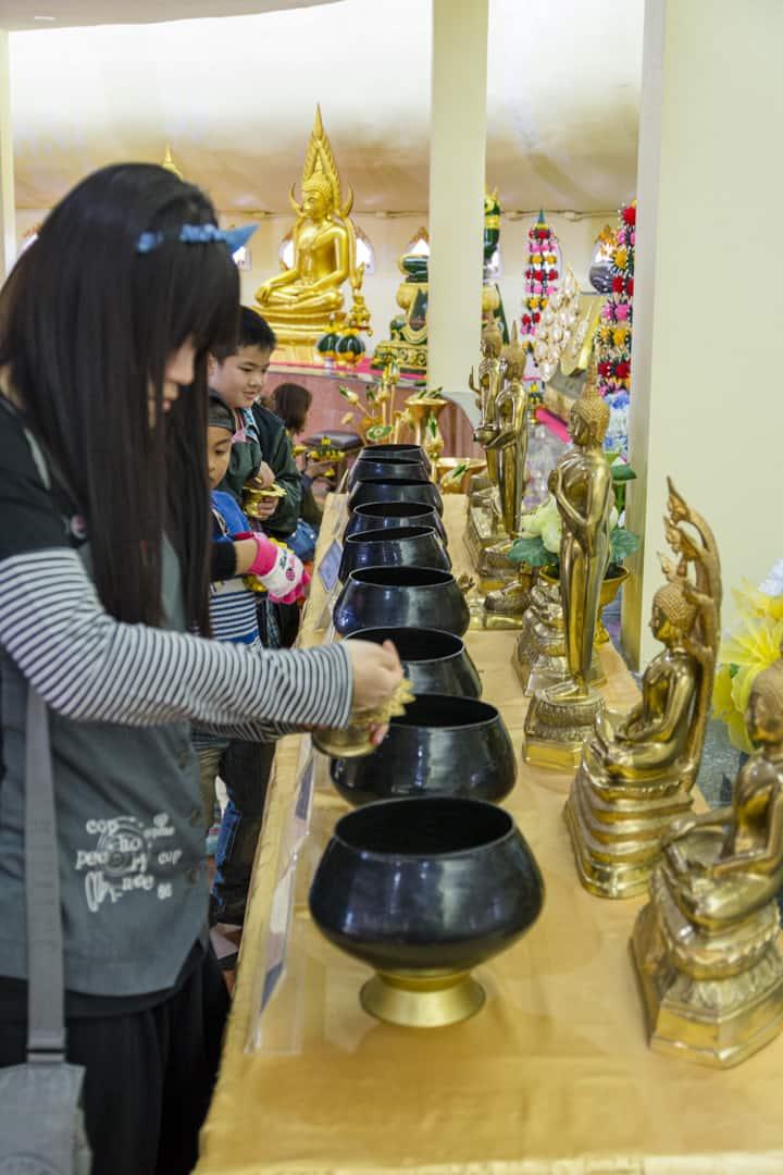 Gläubige spenden vor ihrem Geburts-Buddha