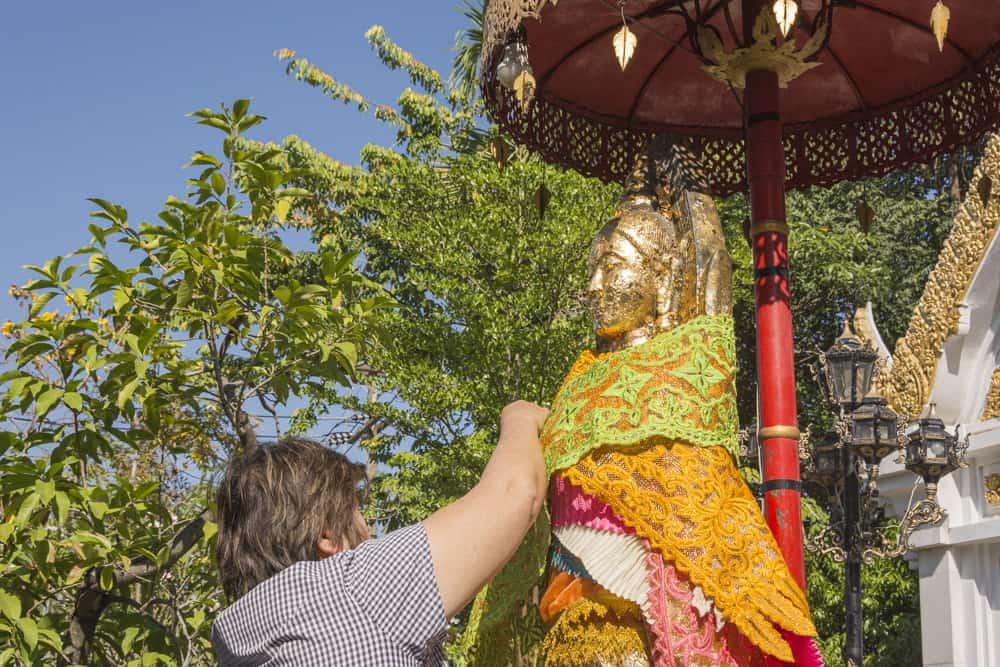 Aufkleben von Blattgold an den außen stehenden Figuren von Phra Mae Ya