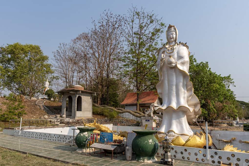Besonderer weißer stehende Buddha mit Naga-Schlangen im Wassergraben