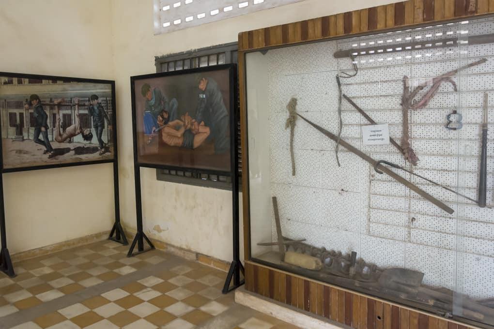Vitrinen mit Folterwerkzeugen und Bilder der Folterungen im Gefängnis S-21 - Foto im Tuol-Sleng-Genozidmuseum Phnom Penh
