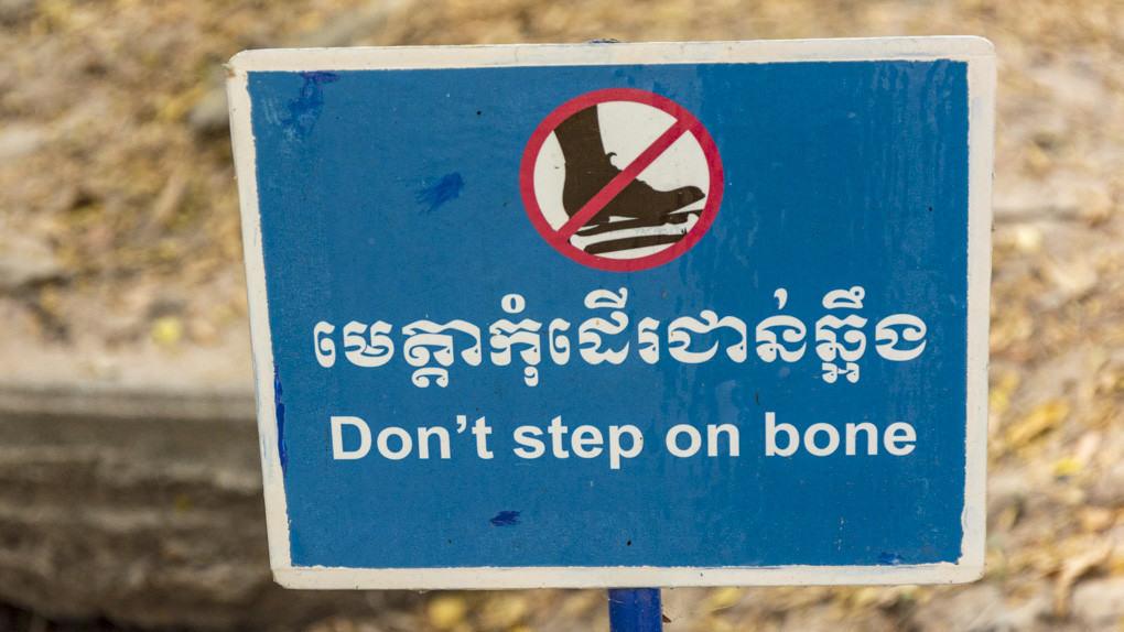 """Schild mit der Aufschrift """"Nicht auf die Knochen treten!"""" in der Gedenkstätte Choeung Ek nahe Phnom Penh in Kambodscha"""