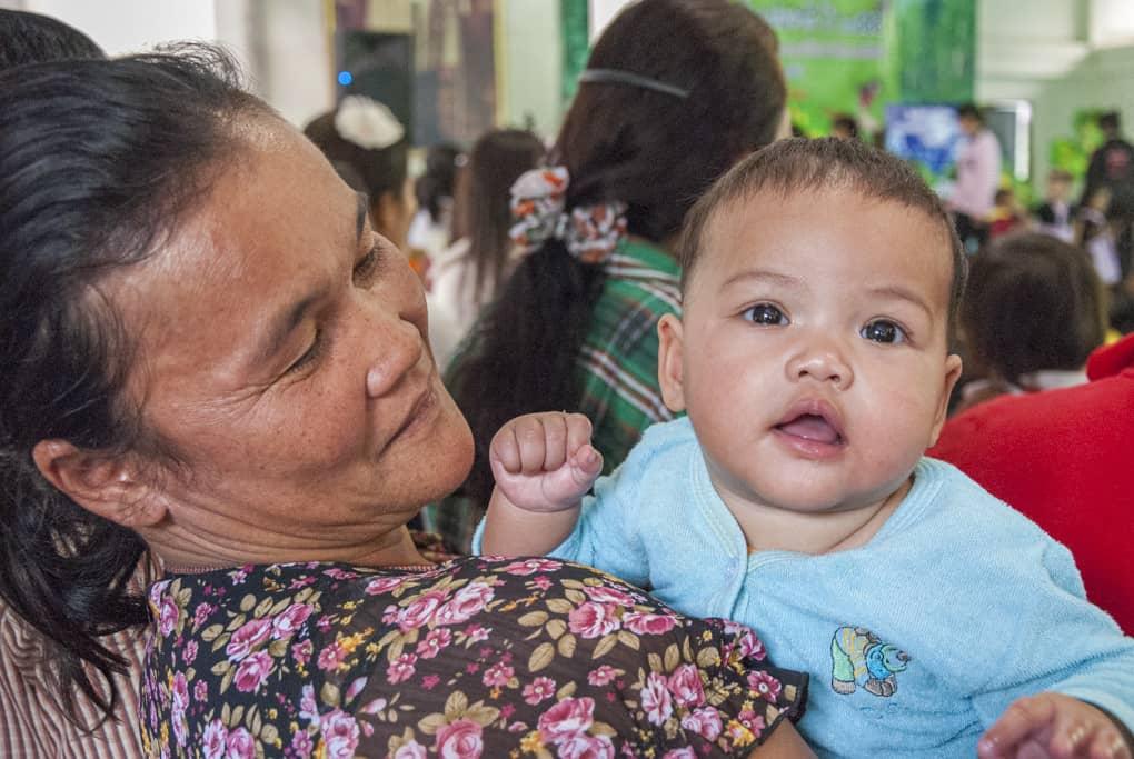 Baby auf dem Arm der Oma in Thailand