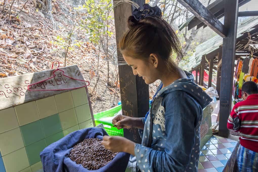 Junge Frau aus Myanmar die kleine Kerne zu Schmuckstücken auffädelte