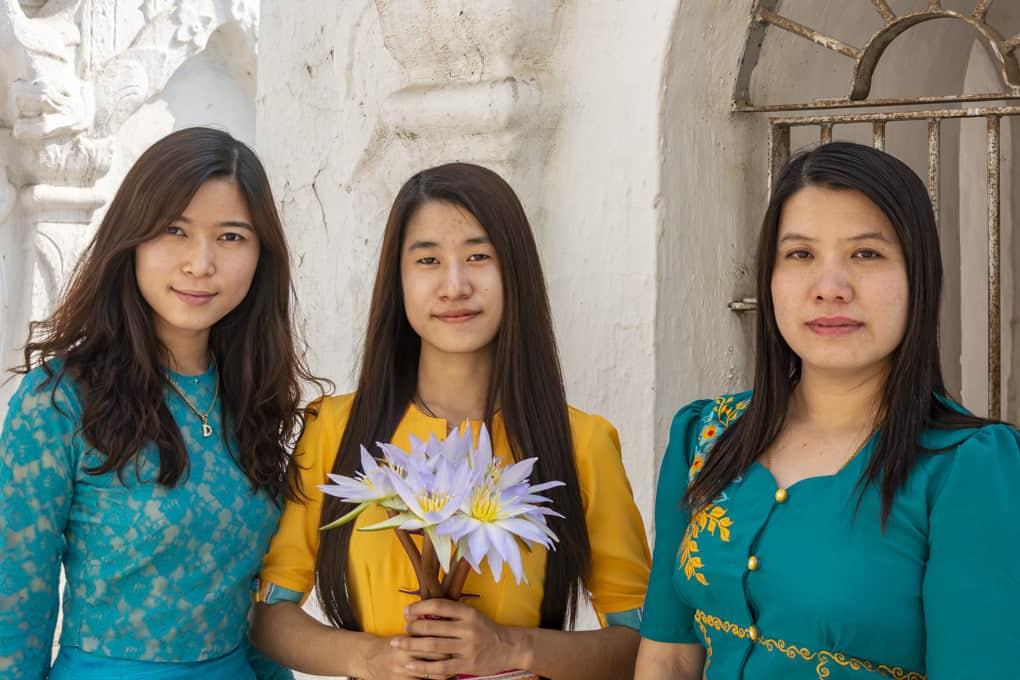 Drei junge Damen aus Myanmar legen Lotos-Blüten zu Ehren Buddhas ab